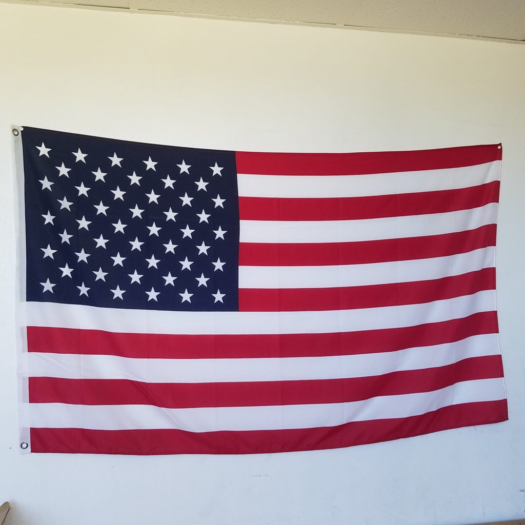 3x5 American flag pinned to wall.
